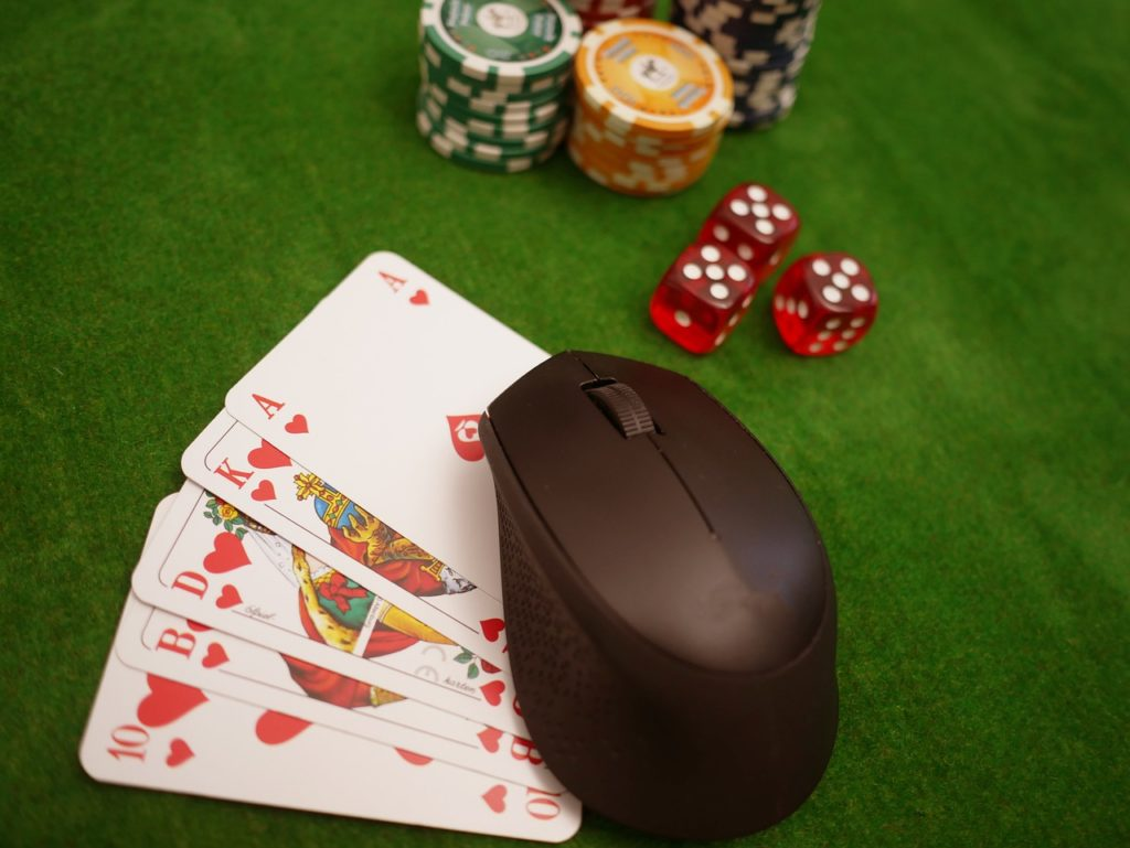 Chips, Würfel und eine Computermaus auf Spielkarten